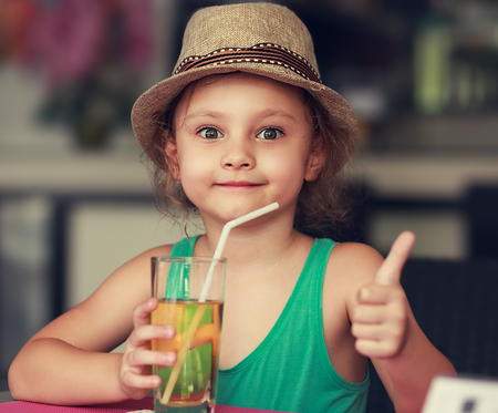57057824 - happy kid girl drinking apple juice in restaurant and showing thumb up sign